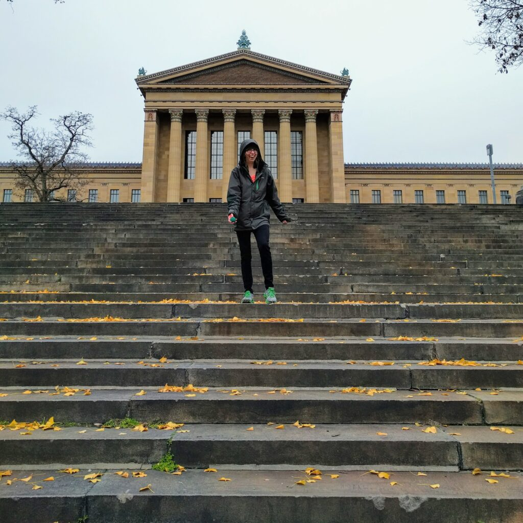 A person with a maniacal grin is preparing to toss a racquetball down the stairs behind the Philadelphia Museum of Art. It looks cold and wintry, with leaves on the ground. She is wearing a jacket and leggings.
